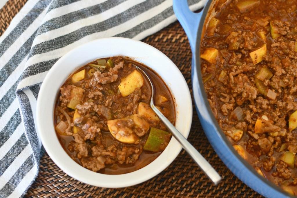 bowl of keto goulash next to pot of goulash