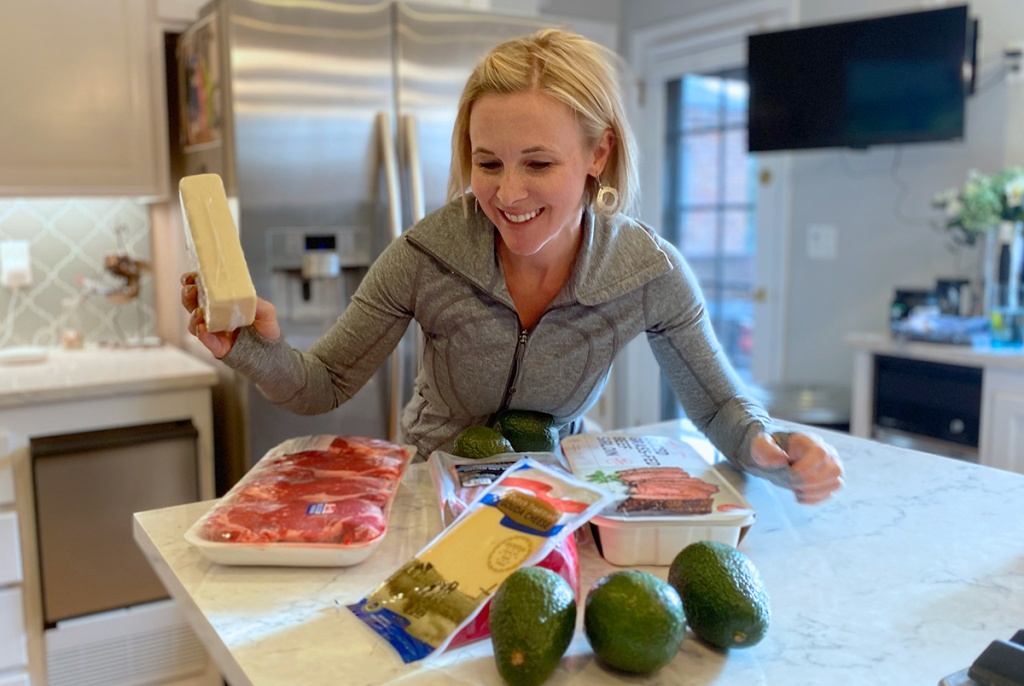 woman in kitchen with meats, cheese, and other keto foods