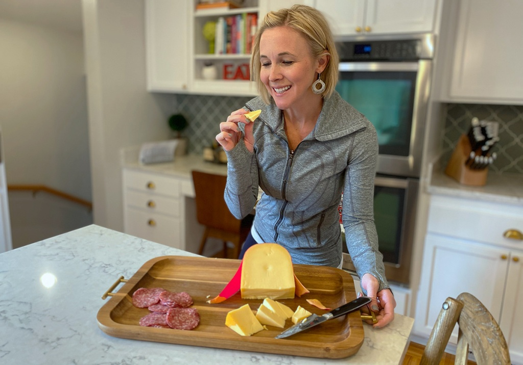 woman with cheese board and piece of cheese in hand
