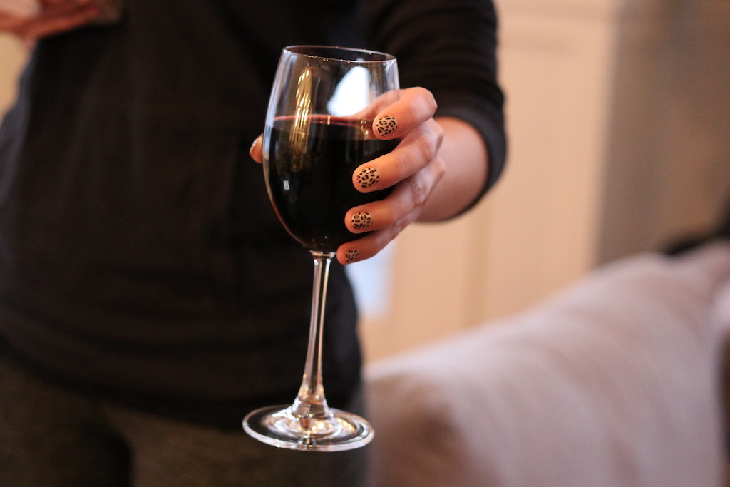 woman holding wine glass with leopard print nails