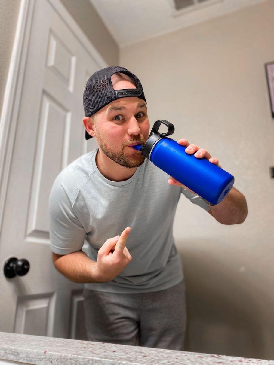 man drinking blue water bottle