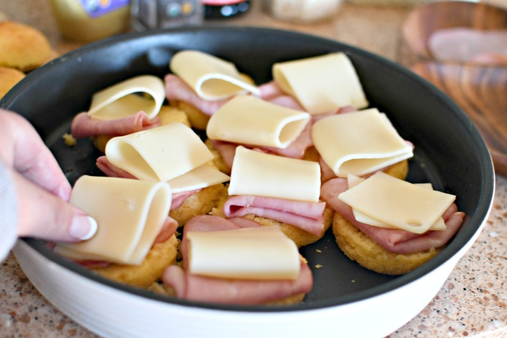 placing cheese on ham and cheese sliders