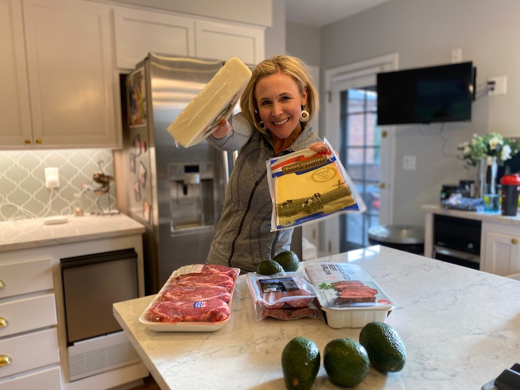 woman holding cheese with steak and avocados on counter