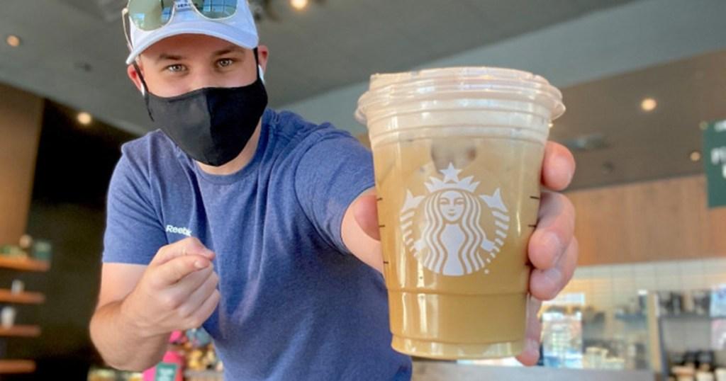 man holding starbucks cup