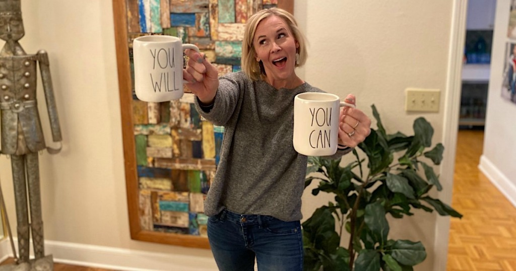 woman holding You Will and You Can coffee mugs