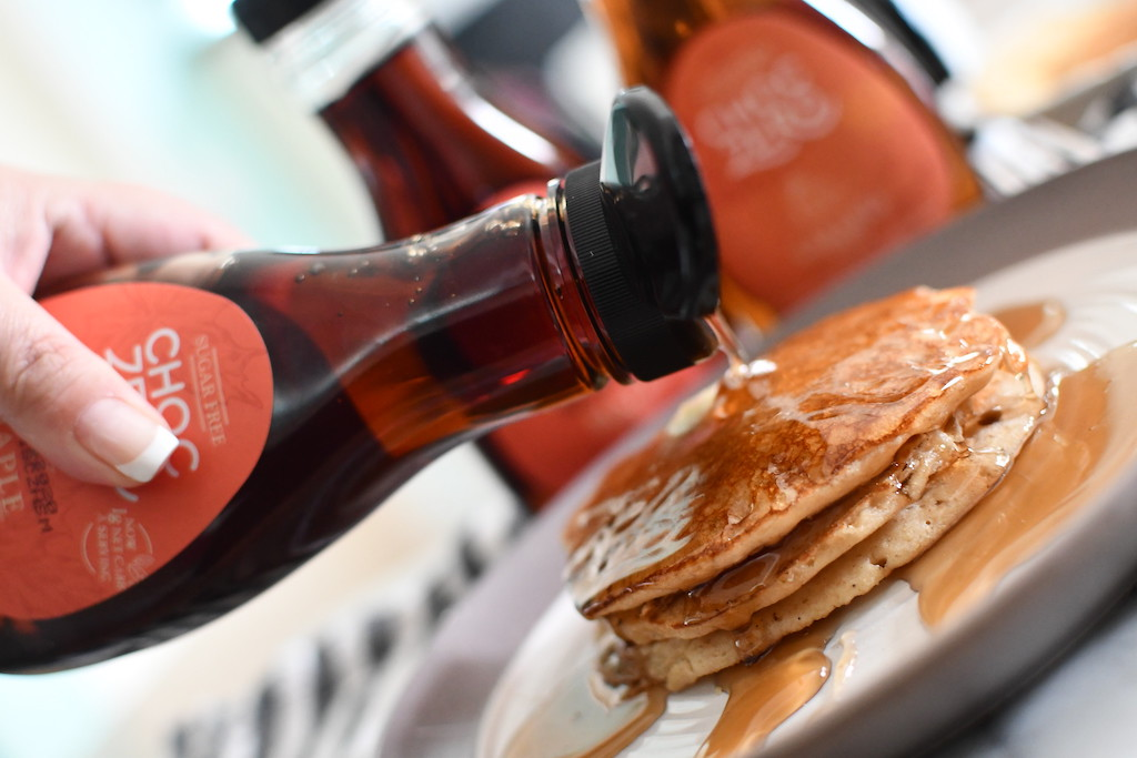 pouring ChocZero keto maple syrup over pancakes