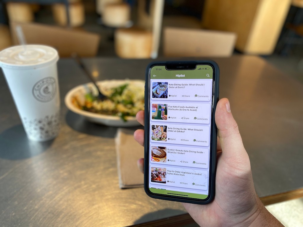 holding smartphone at a restaurant with Hip2Keto app on the screen