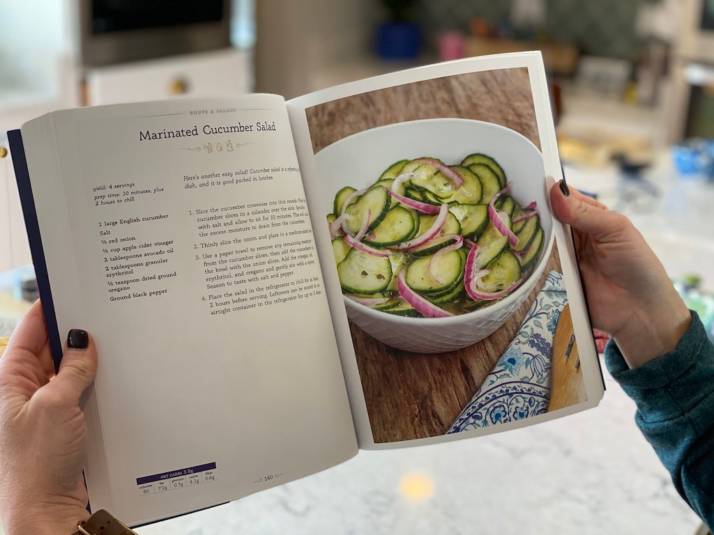 woman holding open cookbook with cucumber salad recipe