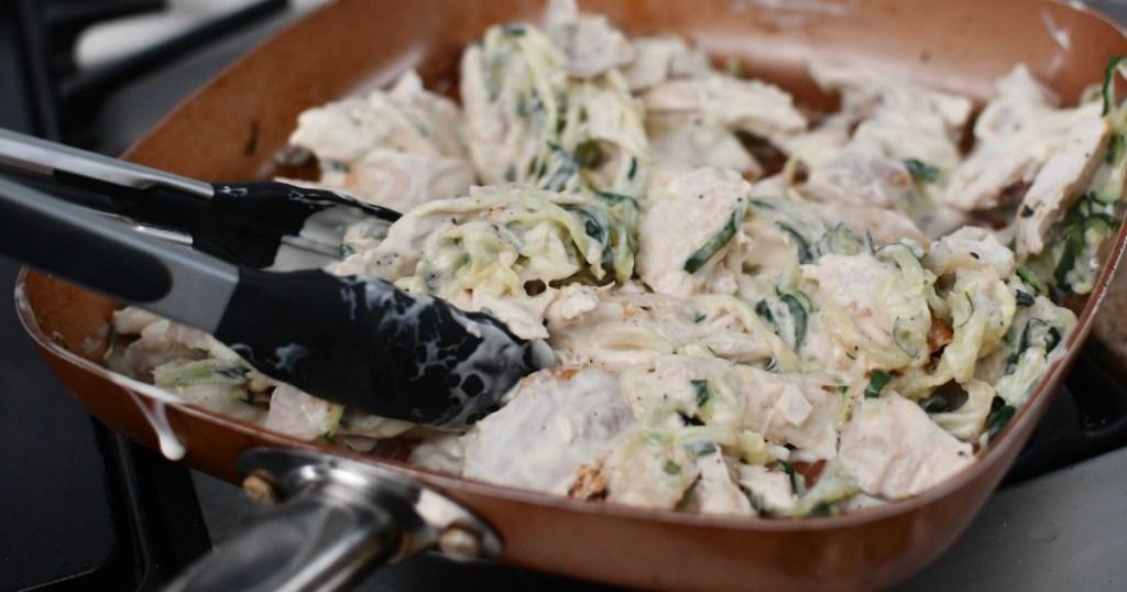 usinng tongs to mix keto chicken alfredo in pan