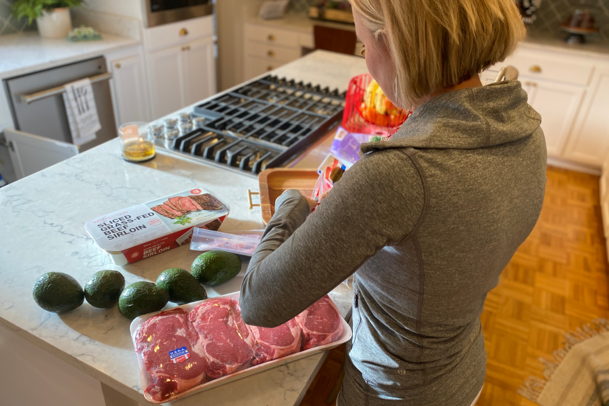 woman standing over counter with beef, avocados, and other keto groceries
