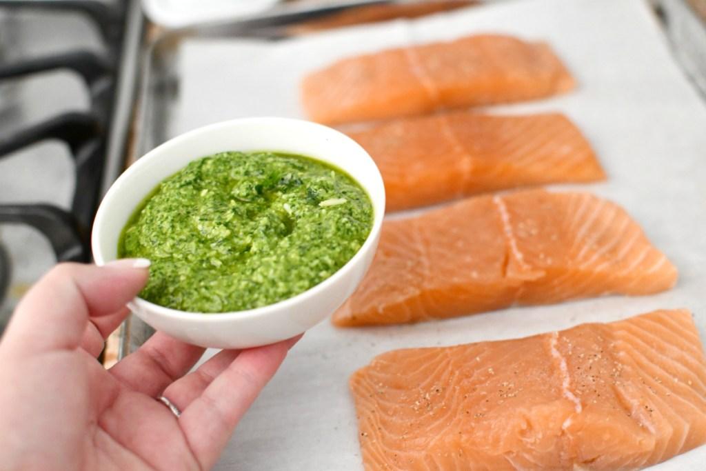 pesto in a bowl next to salmon