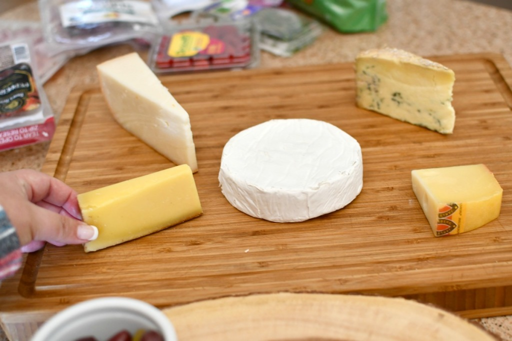 placing a variety of cheeses on a board