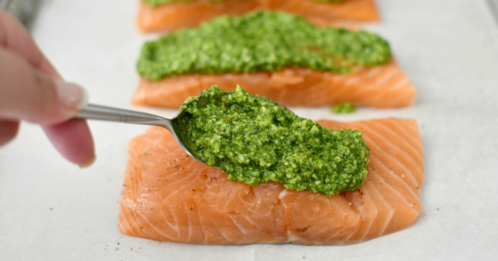 placing pesto on the keto salmon