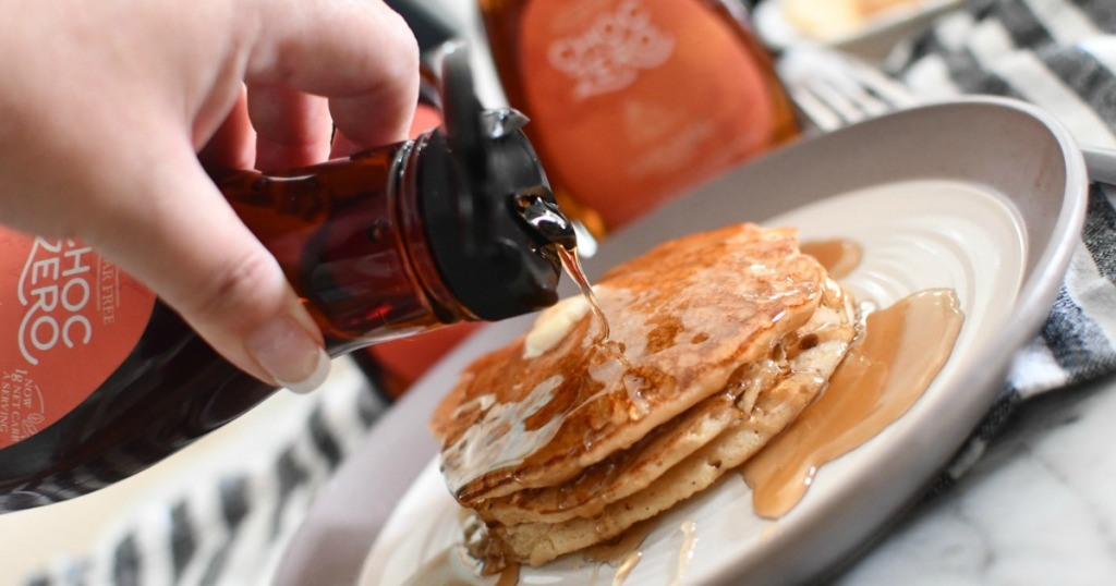 pouring ChocZero maple syrup onto keto pancakes