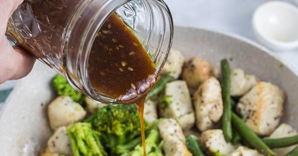 pouring keto teriyaki sauce over stir fry