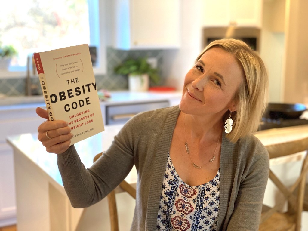 woman holding The Obesity Code book