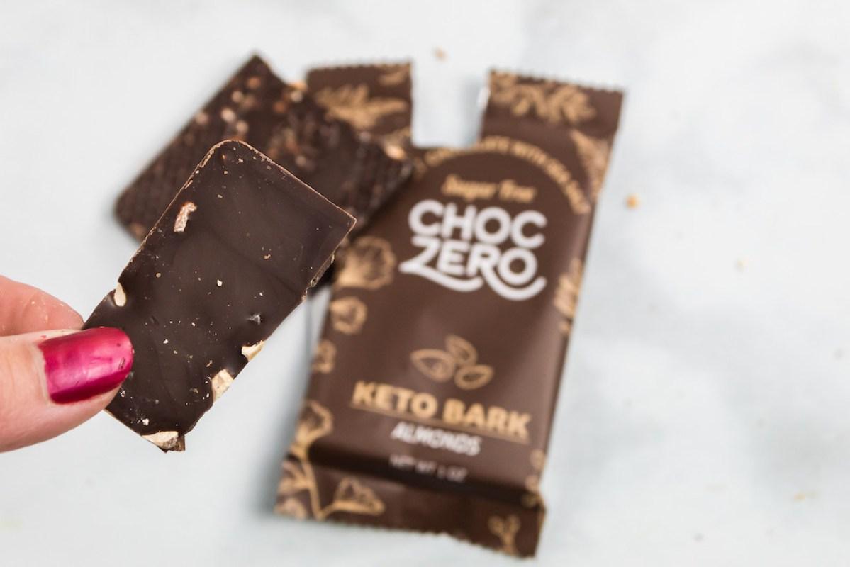 holding piece of ChocZero keto bark chocolate