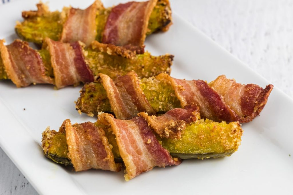 bacon wrapped pickles on a plate