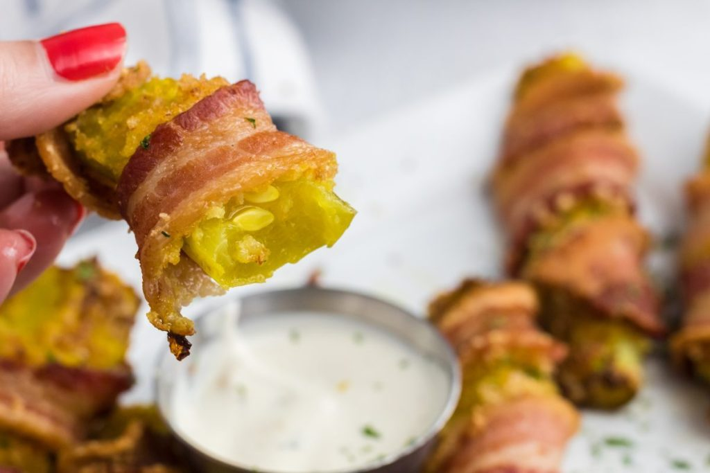 dipping a bacon wrapped pickle spear into ranch
