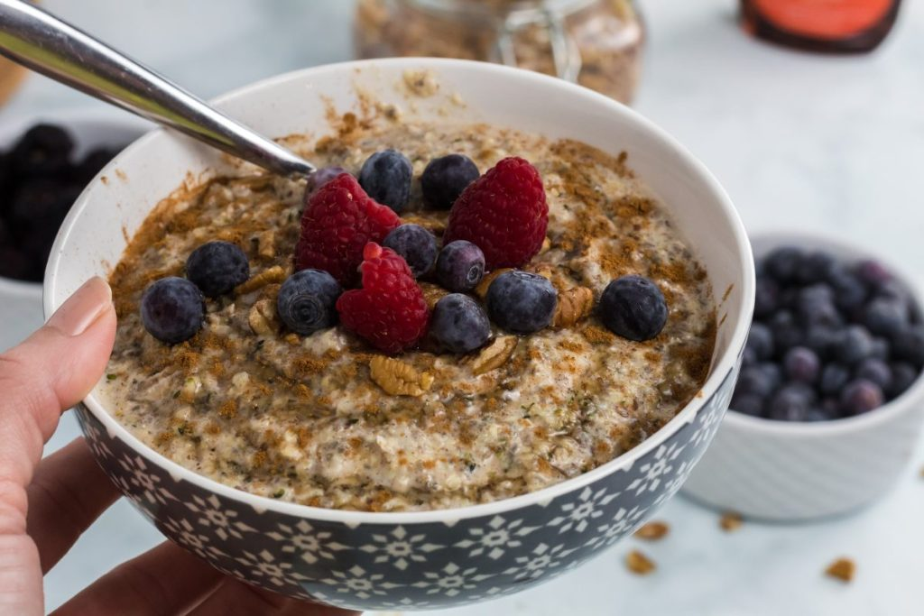 holding bowl of keto oatmeal with berries