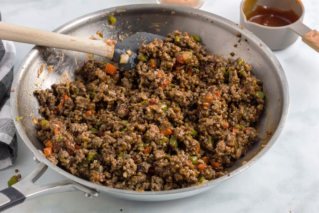 browned ground beef and veggies in pan