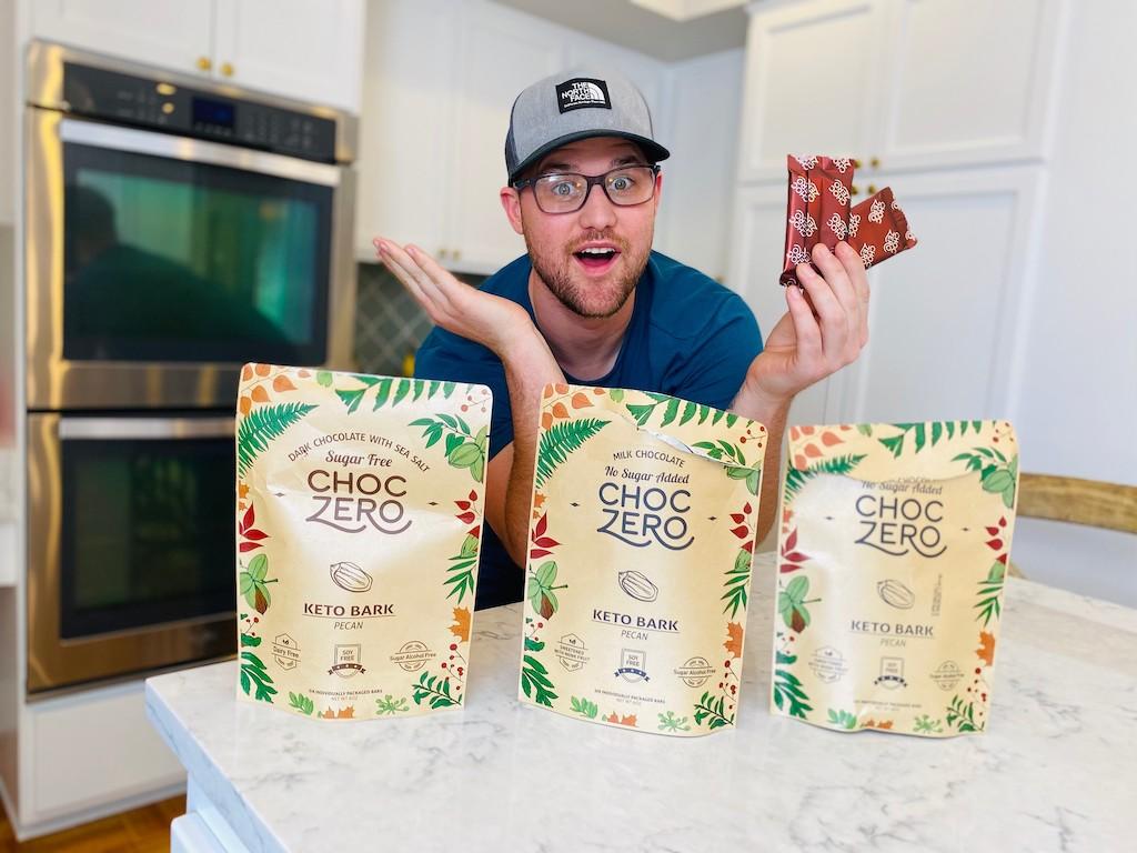 man with ChocZero keto bark bags in kitchen