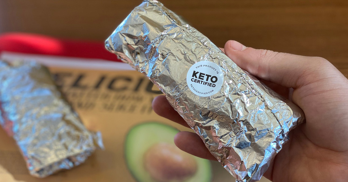 hand holding wrapped taco with keto certified sticker on it