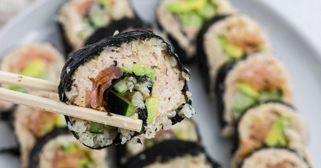 chopsticks holding keto sushi roll piece