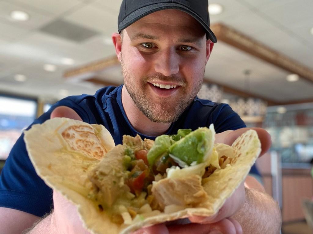 man holding el pollo loco keto taco