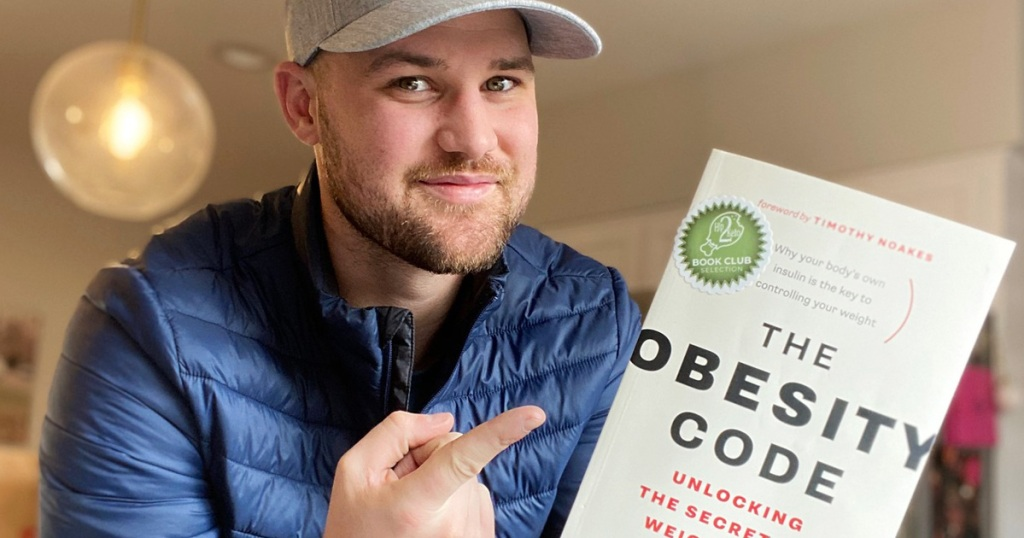 man holding obesity code book