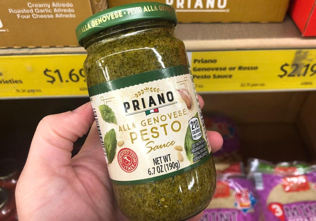 hand holding jar of priano pesto