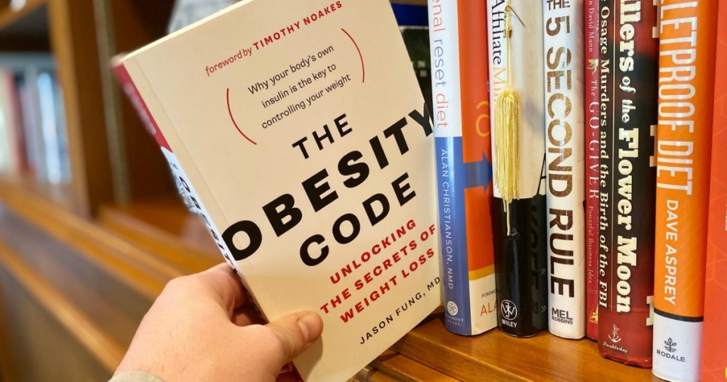 pulling The Obesity Code book off of shelf