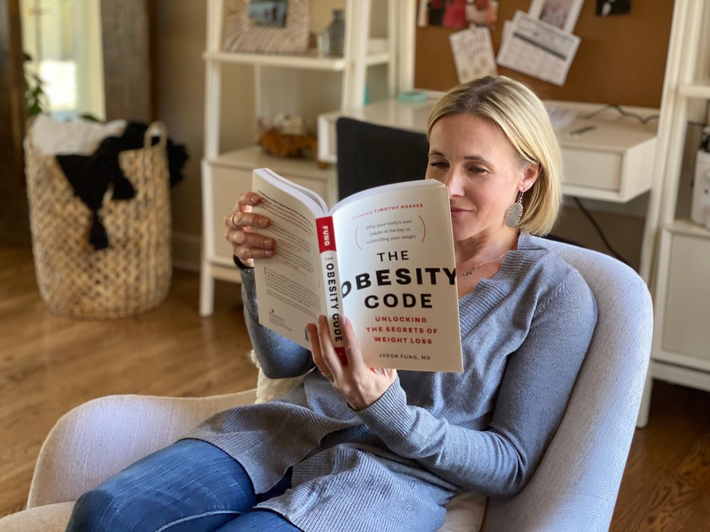 woman reading The Obesity Code book on chair
