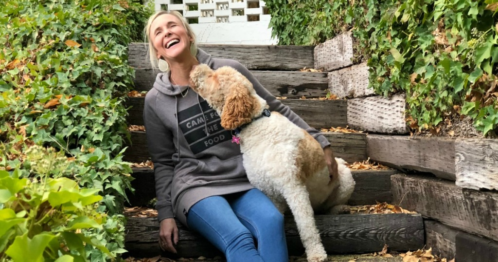 woman laughing on front porch as dog is licking her