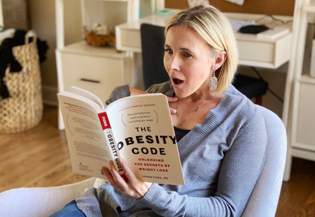 woman reading obesity code book