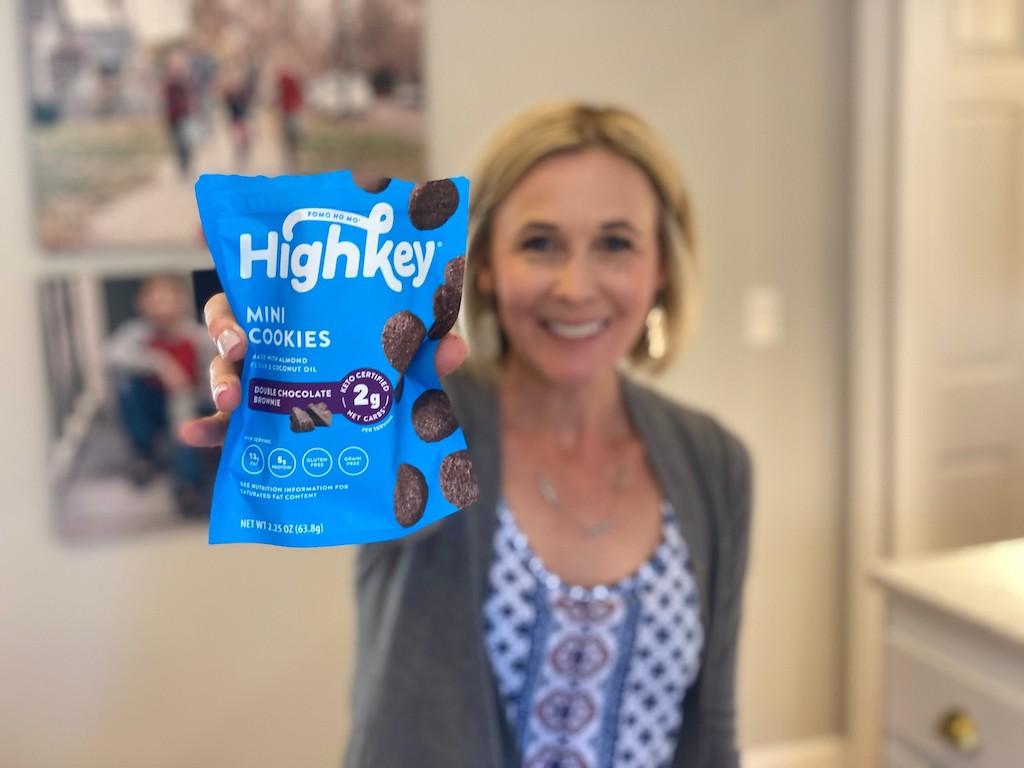 woman holding bag of HighKey mini cookies