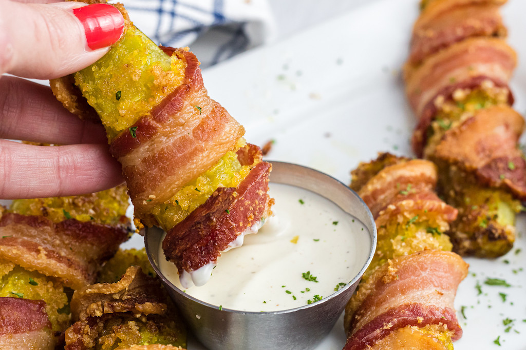 dipping bacon-wrapped pickle in ranch dressing