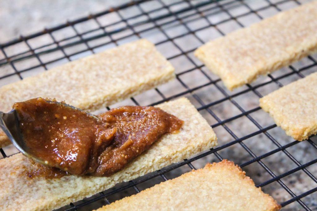 spreading caramel filling on shortbread cookie