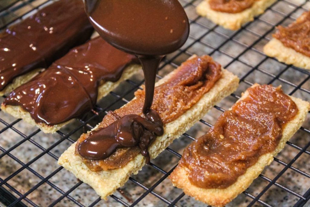 pouring melted chocolate over shortbread cookie bars