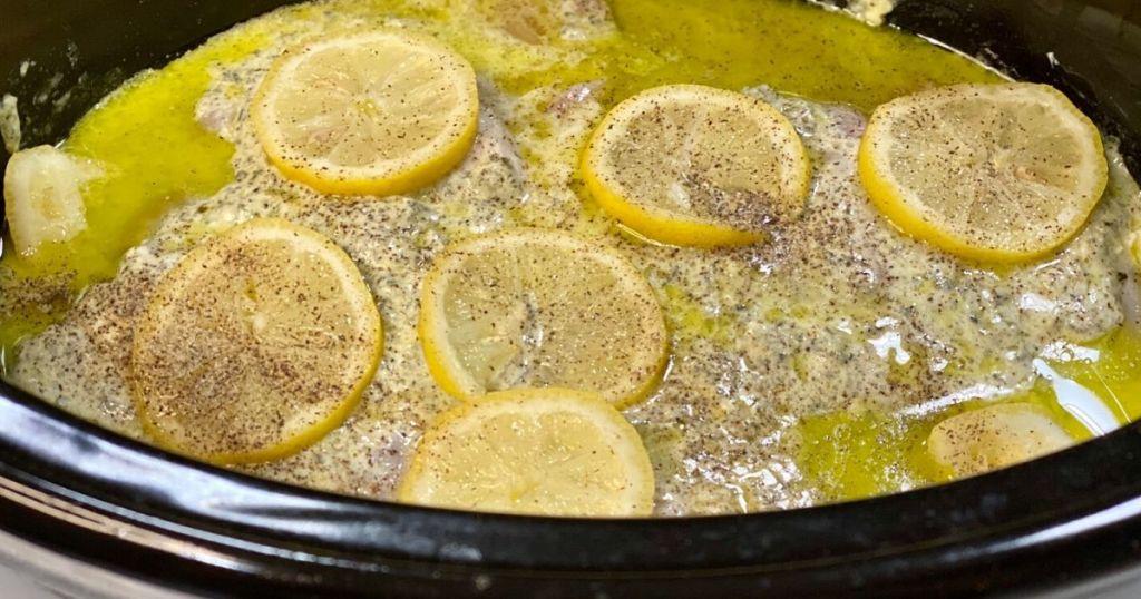 Keto lemon pesto chicken simmering in the slow cooker