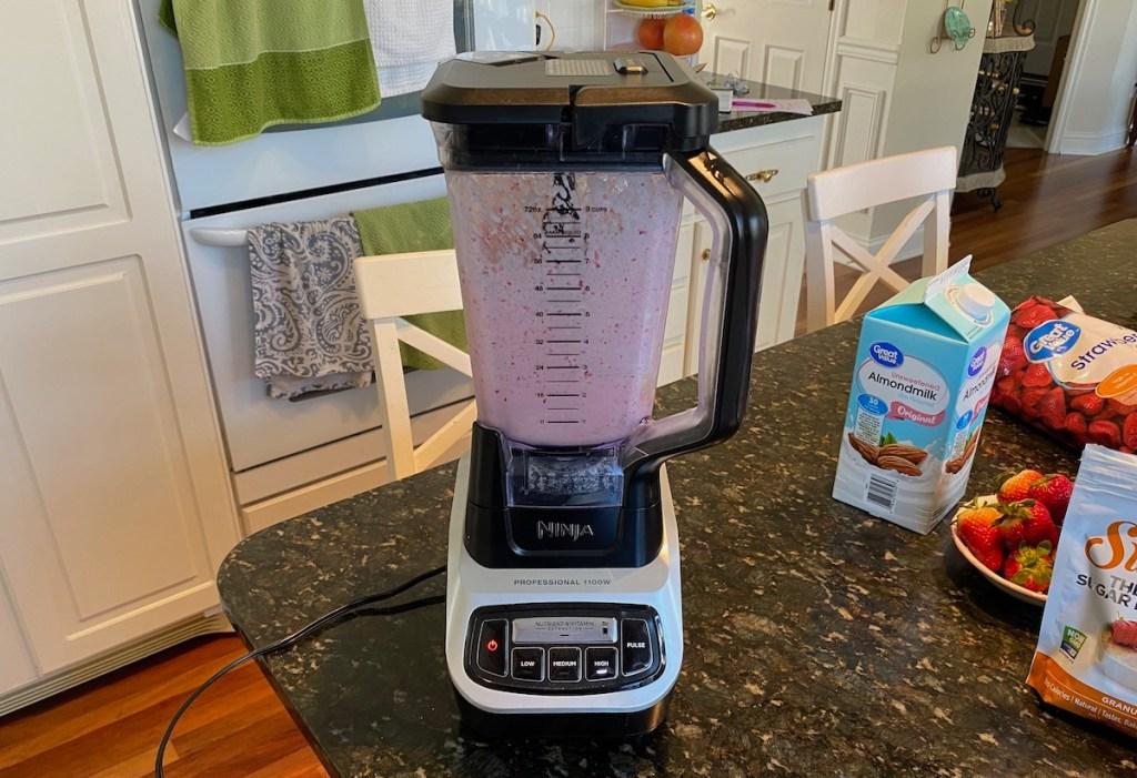 blender with milkshake ingredients mixing inside