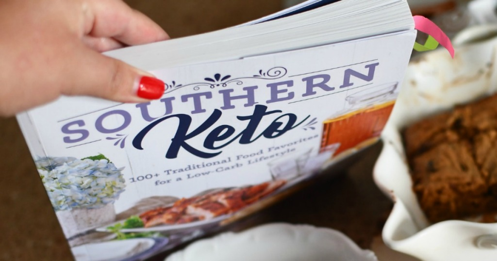 holding Southern Keto Cookbook with keto bars in the background