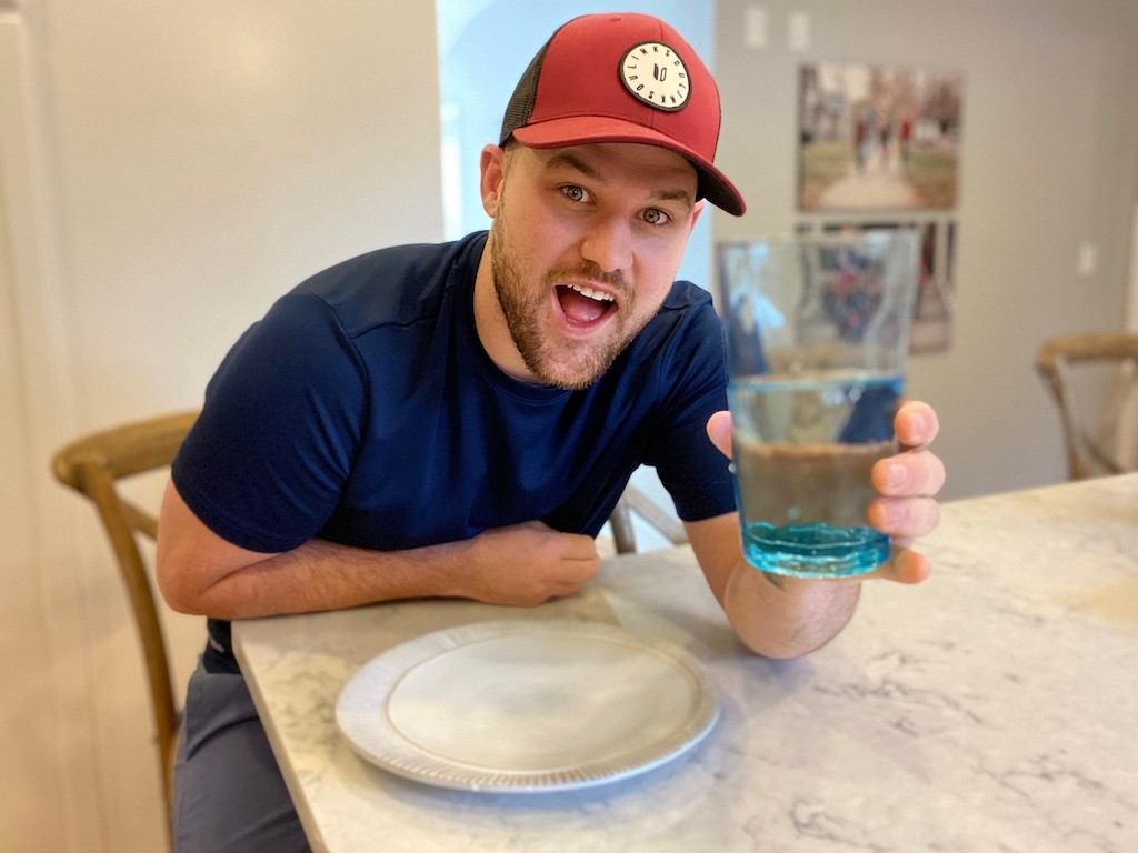 man holding a blue glass of water