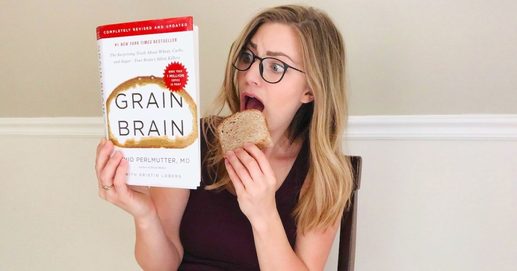 woman eating a slice of bread while reading grain brain book