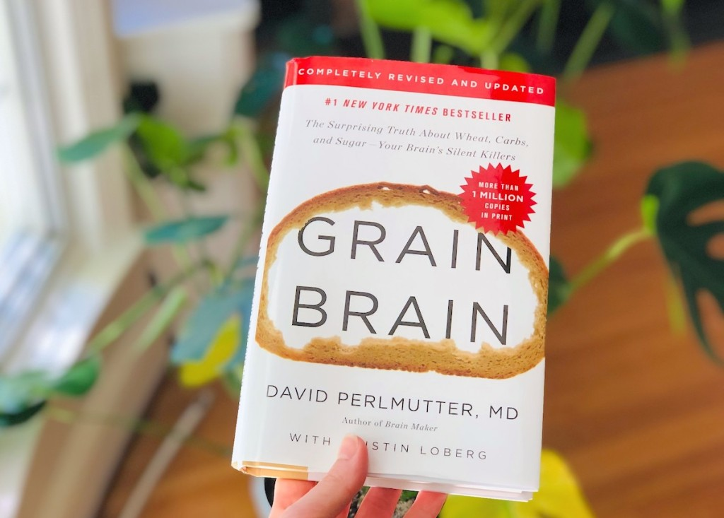 hand holding a Grain Brain book in front of plant