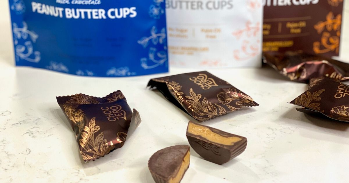 A chocZero peanut butter cup cut in half next to more chocolate on a counter
