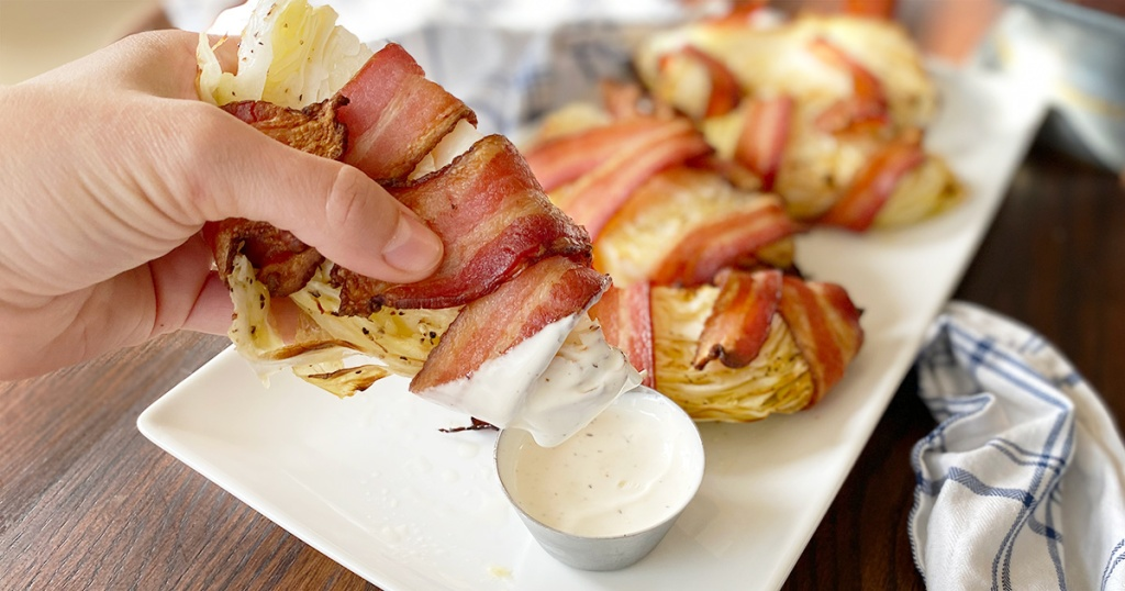 hand holding bacon wrapped cabbage wedge and dipping it in ranch