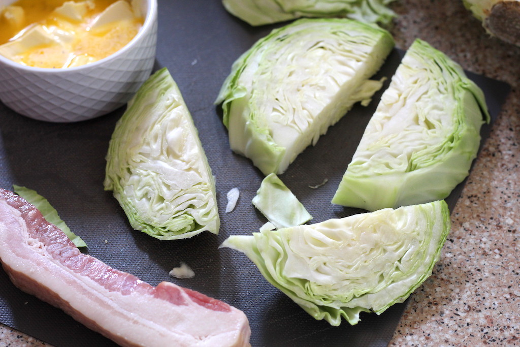 cabbage wedges with bacon and butter on counter