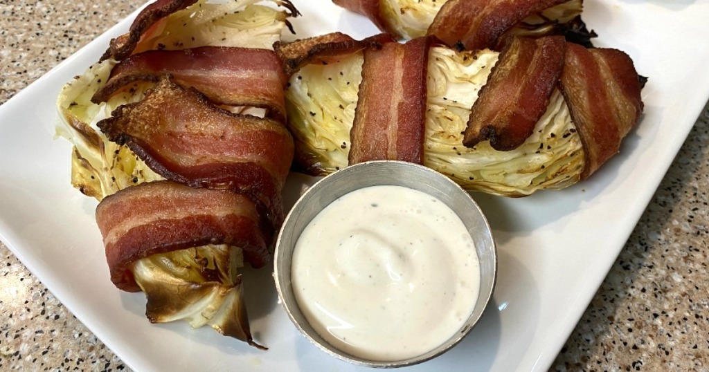 bacon wrapped cabbage wedges on plate with ranch dressing