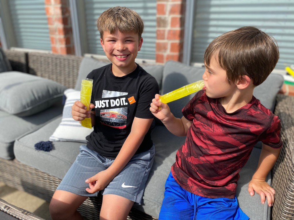two boys eating pickle juice pops